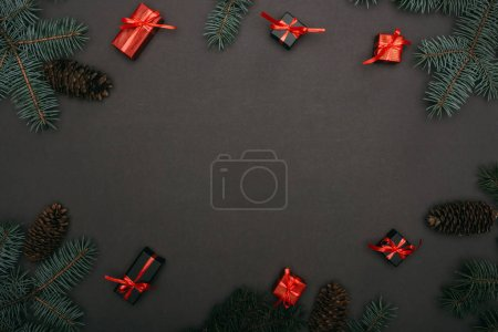 Photo for Top view of christmas gift boxes with spruce branches and pine cones on black - Royalty Free Image