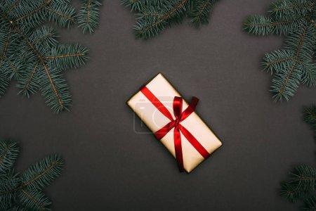 Photo pour Vue du dessus du cadeau de Noël avec des branches d'épinette sur noir - image libre de droit