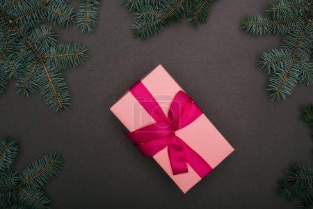Photo pour Haut de la page cadeau de Noël rose avec branches d'épinette sur noir - image libre de droit