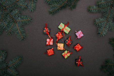 Photo for Top view of little gift boxes with spruce branches on black - Royalty Free Image