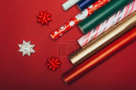 Photo pour Vue du dessus des rouleaux et arcs de papier d'emballage sur rouge - image libre de droit