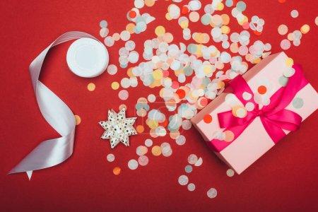 Photo pour Vue du dessus d'un cadeau de Noël avec arc, ruban et confettis sur rouge - image libre de droit