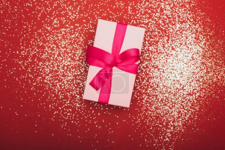 Photo for Top view of one christmas gift with golden confetti on red - Royalty Free Image