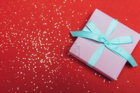 Photo pour Vue du dessus d'un cadeau de Noël avec confettis dorés sur rouge - image libre de droit