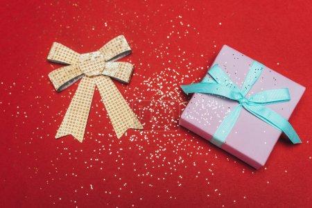 Photo pour Top vue d'un Noël présent avec arc doré et confettis sur rouge - image libre de droit