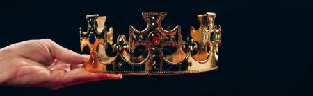 cropped view of woman holding golden crown with gemstones, isolated on black, panoramic shot