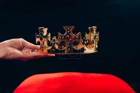 Photo pour Vue croisée d'une femme tenant une couronne dorée avec des pierres précieuses sur un oreiller rouge, isolée sur noir - image libre de droit