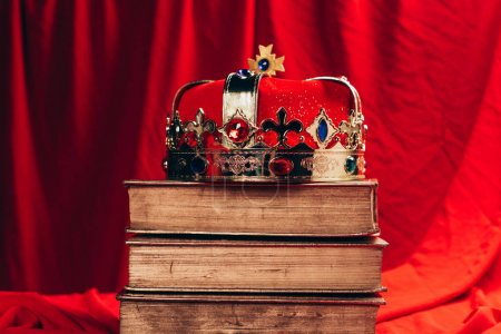 ancient golden crown with gemstones on vintage books on red cloth