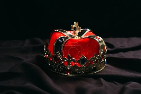Photo for Ancient red golden crown with gemstones on black cloth - Royalty Free Image