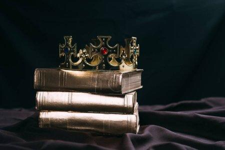 Photo pour L'ancienne couronne dorée avec des pierres précieuses sur les livres sur tissu noir - image libre de droit