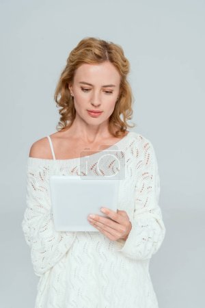 Photo for Attractive woman in sweater using digital tablet isolated on grey - Royalty Free Image