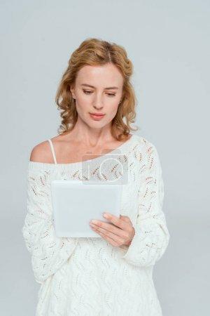 Photo pour Attrayant femme en pull en utilisant tablette numérique isolé sur gris - image libre de droit