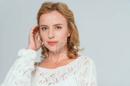 Photo for Attractive woman in sweater looking at camera isolated on grey - Royalty Free Image