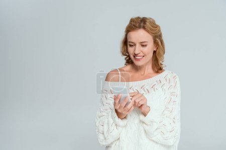 Photo for Attractive and smiling woman using smartphone isolated on grey - Royalty Free Image