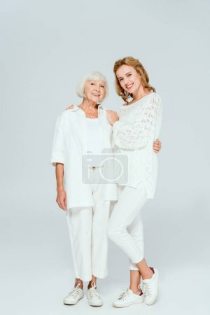 Photo for Attractive mother and daughter smiling and hugging on grey background - Royalty Free Image