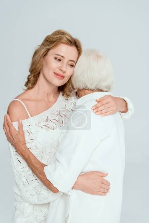 Photo for Back view of mother hugging attractive daughter isolated on grey - Royalty Free Image
