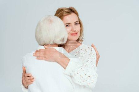 Photo pour Vue arrière de la mère embrassant fille souriante isolée sur gris - image libre de droit