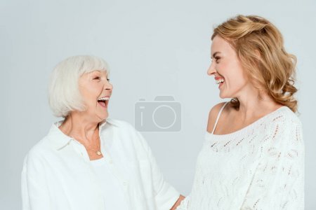 Photo for Attractive mother and smiling daughter looking at each other isolated on grey - Royalty Free Image