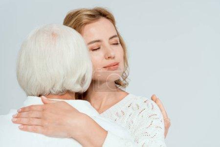 Photo pour Vue arrière de la mère étreignant jolie fille isolée sur gris - image libre de droit