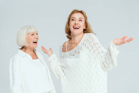 Photo for Attractive mother looking at smiling daughter with outstretched hands isolated on grey - Royalty Free Image