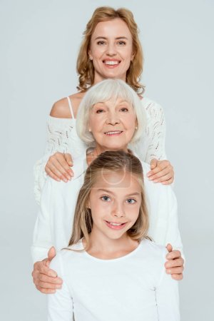 Photo for Smiling mother, grandmother and granddaughter hugging isolated on grey - Royalty Free Image