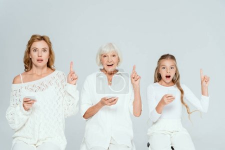 Photo for Shocked granddaughter, mother and grandmother holding smartphones and showing idea gestures isolated on grey - Royalty Free Image