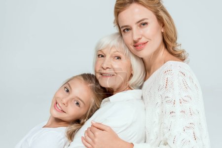 Photo for Smiling granddaughter, mother and grandmother hugging isolated on grey - Royalty Free Image
