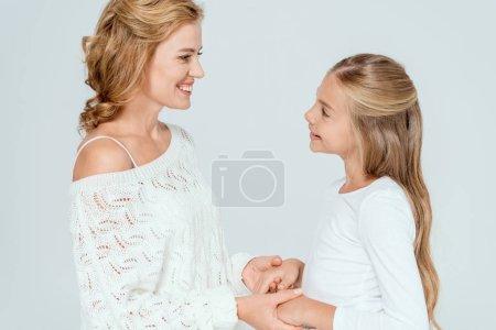 Foto de Vista lateral de la atractiva madre y la hija sonriente con las manos aisladas en gris. - Imagen libre de derechos