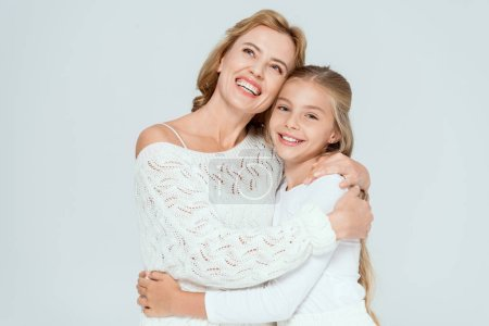 Photo for Attractive mother hugging smiling daughter and looking up isolated on grey - Royalty Free Image