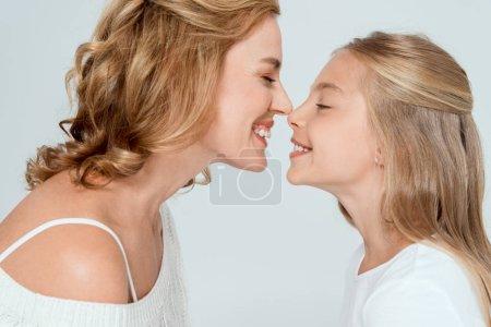 Photo pour Vue latérale de la belle mère touchant le nez de la fille souriante isolée sur gris - image libre de droit