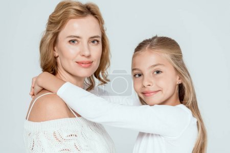Photo for Smiling daughter  hugging attractive mother and looking at camera isolated on grey - Royalty Free Image