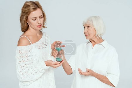 Photo for Attractive mother giving hourglass to daughter isolated on grey - Royalty Free Image