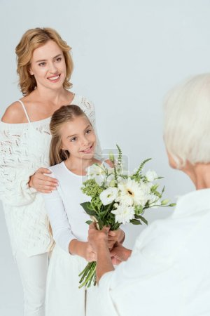 smiling granddaughter giving bouquet to grandmother isolated on grey