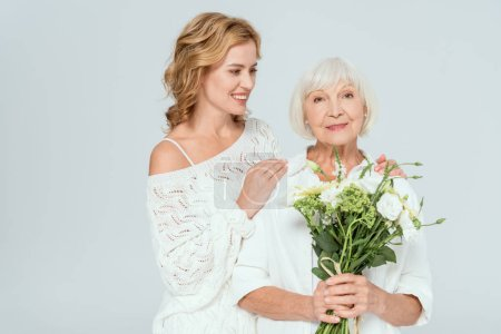 Photo for Smiling daughter hugging attractive mother with bouquet isolated on grey - Royalty Free Image