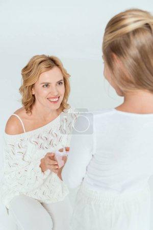 Photo for Back view of daughter giving gift to smiling mother isolated on grey - Royalty Free Image