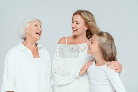 Photo for Smiling mother hugging granddaughter and looking at grandmother isolated on grey - Royalty Free Image