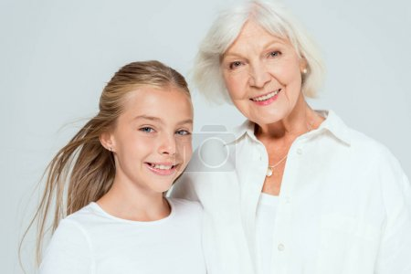 Photo for Smiling granddaughter and grandmother looking at camera isolated on grey - Royalty Free Image