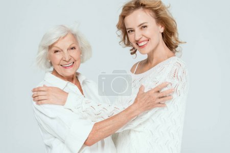 Photo pour Smiling mother and daughter hugging and looking at camera isolated on grey - image libre de droit