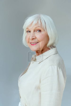 attractive and smiling woman looking at camera isolated on grey