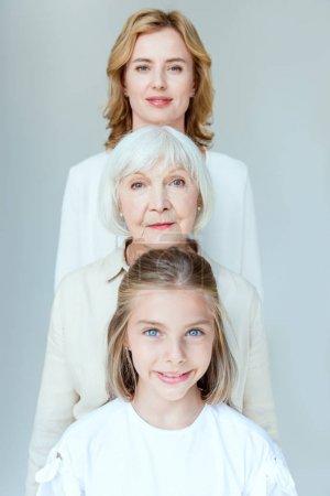 Photo pour Petite-fille, grand-mère et mère souriantes regardant la caméra isolée sur - image libre de droit