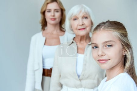 Photo for Selective focus of smiling granddaughter and grandmother, mother on background isolated on grey - Royalty Free Image