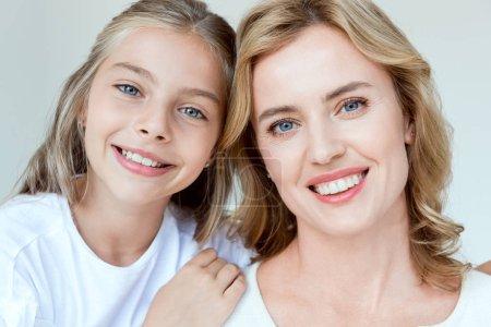 Photo pour Belle mère et sa fille souriante regardant la caméra isolée sur gris - image libre de droit