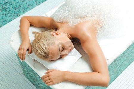 Photo pour Vue à grand angle d'une femme séduisante avec mousse dans un bain turc - image libre de droit