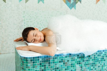 Photo pour Attractive woman lying on hammam table with foam in turkish bath - image libre de droit