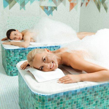 Photo pour Des amis attirants et souriants couchés avec de la mousse dans un bain turc - image libre de droit