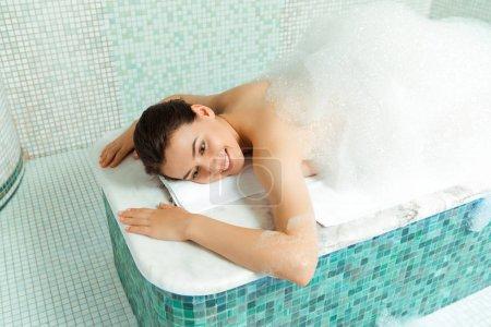 Photo pour Vue à angle élevé d'une femme souriante allongée sur une table de hammam avec mousse dans un bain turc - image libre de droit