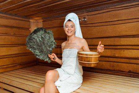 Photo pour Une femme souriante dans des serviettes tenant un balai de bouleau et une baignoire dans un sauna - image libre de droit