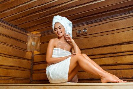 Photo pour Vue à faible angle d'une femme souriante et séduisante dans les serviettes dans le sauna - image libre de droit
