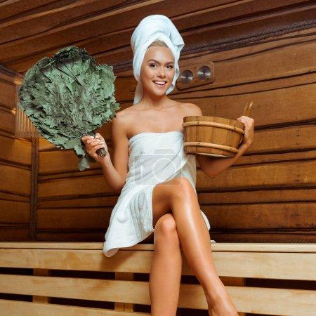 Photo pour Femme souriante et attrayante dans les serviettes tenant baignoire et balai de bouleau dans le sauna - image libre de droit