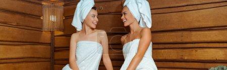Photo pour Plan panoramique d'amis souriants et attrayants en serviettes se regardant dans le sauna - image libre de droit